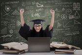 Happy female graduate raise hands in class — Stock Photo