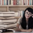 Attractive female student and books at library — Stock Photo