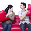 Couple fighting on red sofa - isolated — Stock Photo #27845503