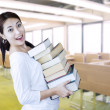 Attractive female student bring pile of books at library — Stock Photo