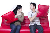 Couple fighting on red sofa - isolated — Stock Photo