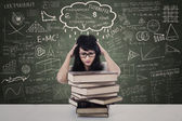 Attractive female stress looking at books in class — Stockfoto