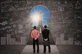 Business partners looking up arrow sign through key hole — Stok fotoğraf
