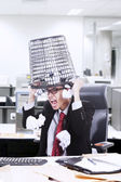 Angry businessman hold rubbish bin on his head at office — Stock Photo
