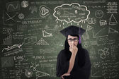 Anxious female graduate thinking of fee in class — Stock Photo