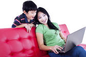 Mother and son quality time on red sofa - isolated — Stock Photo
