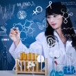 Attractive doctor writing formula on blue — Stock Photo
