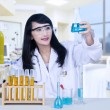 Stock Photo: Beautiful female doctor analysing chemical in hospital