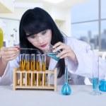 Beautiful scientist pouring liquid at lab — Stock Photo