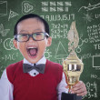 Excited student boy holding trophy in class — Stock Photo