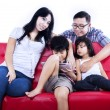 Asian family on red sofa — 图库照片