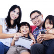 Happy family on red sofa - isolated — 图库照片