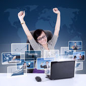 Happy businesswoman raised arms with online pictures at laptop — Stock fotografie