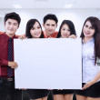 Business team holding blank whiteboard at office — Stock Photo #28653479