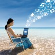 Asian female using laptop at beach — Stock Photo