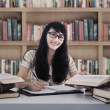Beautiful female student study at library — Stock Photo