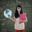 Smart student holding globe with formula background — Stock Photo #28749101