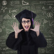 Foto Stock: Excited female graduate and written board