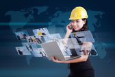 Beautiful contractor calling and using internet on blue — Foto Stock