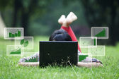 Female lying on grass with laptop and bar chart — Stock Photo