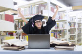 Happy graduate at library with laptop — Stock Photo
