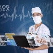 Doctor looking at digital picture on laptop — Stock Photo #28831197
