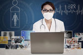 Asian doctor looking at digital photo on laptop — Stock Photo