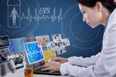 Busy doctor typing on laptop with digital pictures — Stock Photo