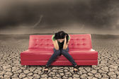 Hopeless female on red sofa at dry ground — Stock Photo
