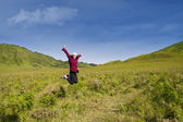 Excited female jumping in grass field — Stock Photo