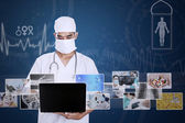 Male doctor working on laptop with digital photo — Stock Photo
