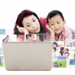 Cute mother and son looking at photos on laptop — Stock Photo #29249503