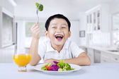 A boy eats vegetable salad in the kitchen — Stock Photo