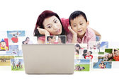 Cute mother and son looking at photos on laptop — Stockfoto
