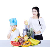 Woman making fruit juice to a boy — Stock Photo