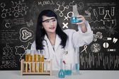 Beautiful scientist holding flask in class — Stock Photo