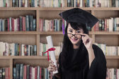 Asian female graduate smiling at library — Stock Photo