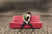 An image of stress female on sofa and dry ground — Stock Photo