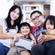 Happy family on red sofa at home — Stockfoto