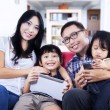 Happy family on red sofa at home — Stock Photo