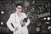 Confident female doctor hold e-tablet on written blackboard — Stock Photo