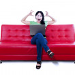 Angry female sitting on red sofa - isolated — Stock Photo