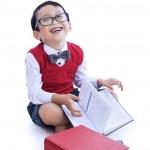 Boy laughing reading books — Stock Photo