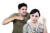 Boyfriend in rage behind girlfriend - isolated — Stock Photo
