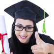 Thumbs up graduation woman — Stock Photo