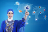 Asian muslim connects to social media on blue — 图库照片