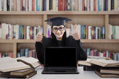 Graduate woman giving thumbs up in library — Stock Photo
