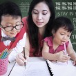 Beautiful teacher help children write letters in class — Stockfoto