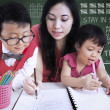 Beautiful teacher help children write letters in class — Stock fotografie