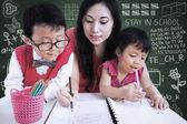 Bella insegnante aiutare i bambini a scrivere lettere in classe — Foto Stock